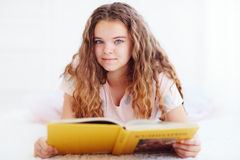 Beautiful young girl reading a book on carpet Royalty Free Stock Images