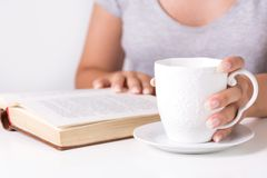 Young woman reading book and holding cup of coffee at home desk stock image