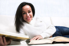 Beautiful young girl reading book lying on the couch. royalty free stock photography