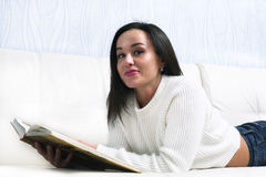 Beautiful young girl reading book lying on the couch. stock photography