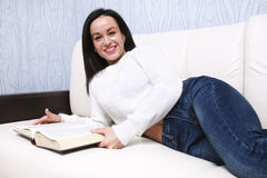 Beautiful young girl reading book lying on the couch. Happy young girl reading a book on the couch Royalty Free Stock Photo