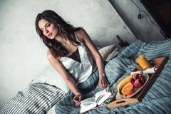 Girl in bed. Beautiful young girl is reading a book while sitting in bed at home, a tray with fruits is near Stock Image