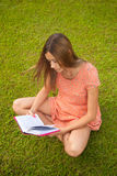 Beautiful young girl reading a book sitting on the grass Royalty Free Stock Photography