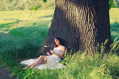 Beautiful young girl reading book while sitting under giant oak. Beautiful young girl sitting on blanket under giant oak and reading book on sunny summer day Stock Photography