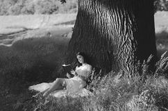 Beautiful young girl reading book under giant oak in summer Royalty Free Stock Images