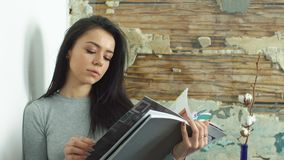 Beautiful young girl reading a glossy magazine stock footage