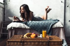 Girl in bed. Beautiful young girl is reading while lying on bed at home, a tray with fruits in the foreground in focus Stock Photo