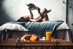 Girl in bed. Beautiful young girl is reading while lying on bed at home, a tray with fruits in the foreground in focus Royalty Free Stock Photos