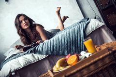 Girl in bed. Beautiful young girl is reading a magazine while lying on bed at home, a tray with fruits in the foreground Royalty Free Stock Images