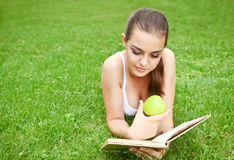 Beautiful young girl reading in summer park Stock Photography