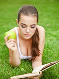 Beautiful young girl reading in summer park Royalty Free Stock Image