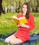 Beautiful young girl reads book in park Royalty Free Stock Photos