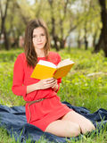 Beautiful young girl reads book in park Stock Images