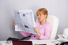 Beautiful young girl reads newspaper Stock Images