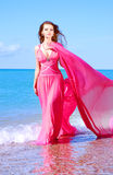 The beautiful young girl in red dress. Goes on water Stock Photo