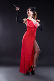 Beautiful young girl in a red dress with a cigarette Royalty Free Stock Photography