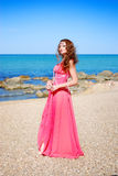 The beautiful young girl in red dress costs. On beach Stock Photos