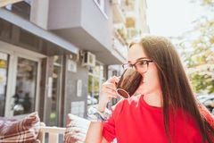 Beautiful young girl in red dress and eyeglasses holding cup with her hand and drinking coffee while she sitting and taking a brea royalty free stock image