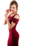 Beautiful young girl in red dress with nectarine in hands Royalty Free Stock Photos