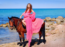The beautiful young girl in red dress sits on hors. A portrait of a caucasian girl with her horse Stock Photo