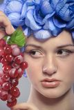 Beautiful young girl with red grapes Stock Photography