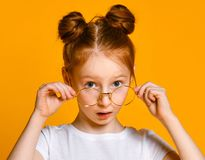 Beautiful young girl with red hair with a bagel in her stylish glasses looks at you in the frame. stock photography