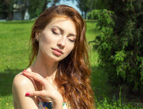 Beautiful young girl with red hair big full lips relaxed resting in the Park Royalty Free Stock Photos