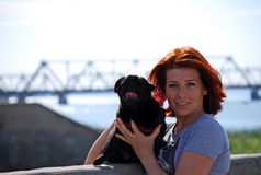 The beautiful young girl with red hair embraces on the street of the pet a black dog of breed a pug. The girl walks with the pet a pug in the sunny warm summer Royalty Free Stock Photography