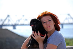 The beautiful young girl with red hair embraces on the street of the pet a black dog of breed a pug. The girl walks with the pet a pug in the sunny warm summer Stock Photo