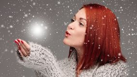 Beautiful young girl with red hair and red nails holding her hands together and blowing on white lightening ball.