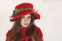 Beautiful young girl in a red hat and a wreath with pine cones in a knitted scarf. Fashion, style, Christmas. Royalty Free Stock Photography