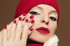 Beautiful young girl. A beautiful young girl with red lipstick and nail Polish on a brown background in the hat royalty free stock photography