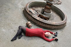 Beautiful young girl in a red mini dress at the dried-up fountain Stock Photo
