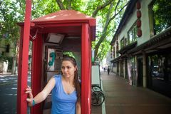 Beautiful young girl in red phone booth somewere on street royalty free stock photography