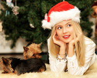Beautiful young girl in red Santa hat near Christmas tree Stock Photos
