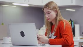 Beautiful young girl in red sweater messaging with friends on the phone. Young beautiful girl sits at the table at kitchen and using her phone. Pretty girl is stock footage