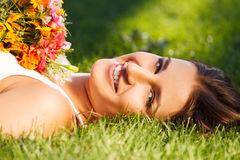 Beautiful young girl relaxing on green grass Royalty Free Stock Image