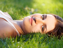 Beautiful young girl relaxing on green grass Royalty Free Stock Photos
