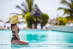 Beautiful young girl relaxing in the swimming pool outdoors Royalty Free Stock Image
