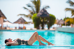 Beautiful young girl relaxing in the swimming pool outdoors Stock Image