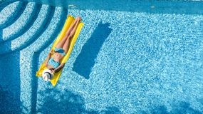 Beautiful young girl relaxing in swimming pool, swims on inflatable mattress and has fun in water on family vacation, aerial view. Beautiful young girl relaxing royalty free stock photos