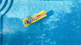 Beautiful young girl relaxing in swimming pool, swims on inflatable mattress and has fun in water on family vacation. Tropical holiday resort, aerial top view stock image