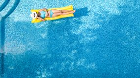 Beautiful young girl relaxing in swimming pool, swims on inflatable mattress and has fun in water on family vacation. Tropical holiday resort, aerial drone royalty free stock photo