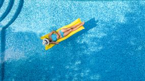 Beautiful young girl relaxing in swimming pool, swims on inflatable mattress and has fun in water on family vacation. Tropical holiday resort, aerial drone stock images
