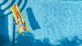 Beautiful young girl relaxing in swimming pool, swims on inflatable mattress and has fun in water on family vacation. Tropical holiday resort, aerial drone royalty free stock images