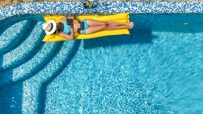 Beautiful young girl relaxing in swimming pool, swims on inflatable mattress and has fun in water on family vacation. Tropical holiday resort, aerial drone royalty free stock image