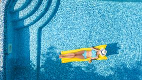Beautiful young girl relaxing in swimming pool, swims on inflatable mattress and has fun in water on family vacation. Tropical holiday resort, aerial drone stock photo