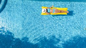 Beautiful young girl relaxing in swimming pool, swims on inflatable mattress and has fun in water on family vacation, aerial view royalty free stock images