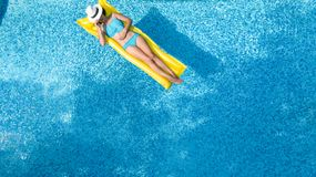 Beautiful young girl relaxing in swimming pool, swims on inflatable mattress and has fun in water on family vacation. Tropical holiday resort, aerial drone royalty free stock photos
