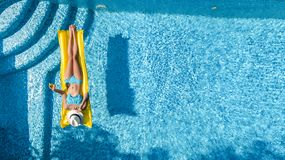 Beautiful young girl relaxing in swimming pool, swims on inflatable mattress and has fun in water on family vacation, aerial view stock image